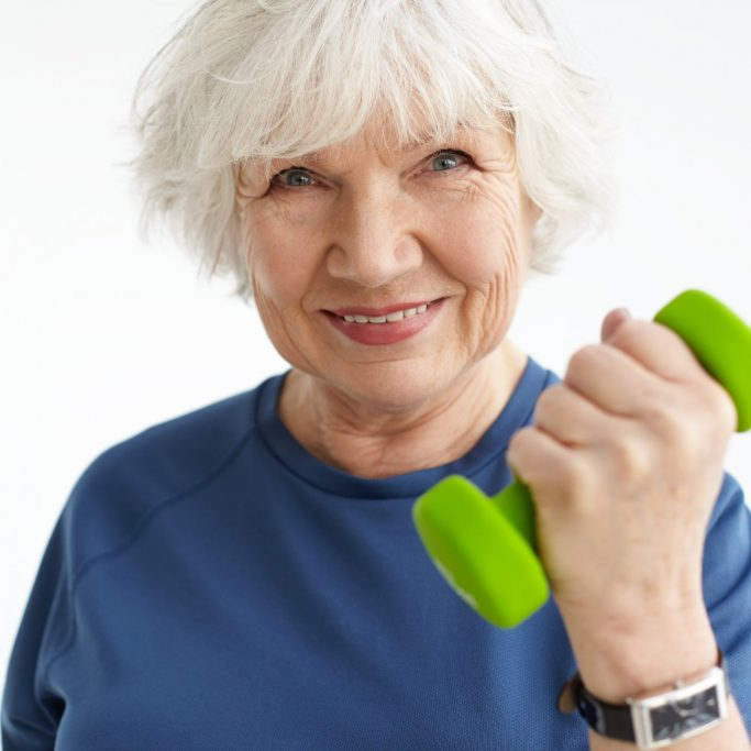 Close up image of energetic sporty mature woman with gray hair and wrinkles exercising indoors, doing bicep curls, holding green dumbbell and smiling happily at camera. Sports, age and fitness
